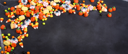 Halloween candy scattered over a black chalkboard background, room for copy space. Foto de archivo