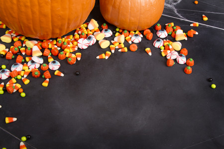 Pumpkins and Halloween candy scattered over a black chalkboard background, room for copy space.