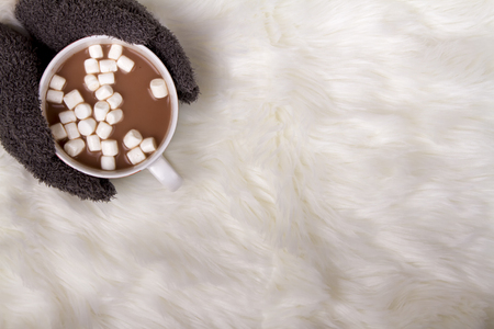 A person holding a mug of hot chocolate or cocoa with marshmallows  on a faux fur background Foto de archivo