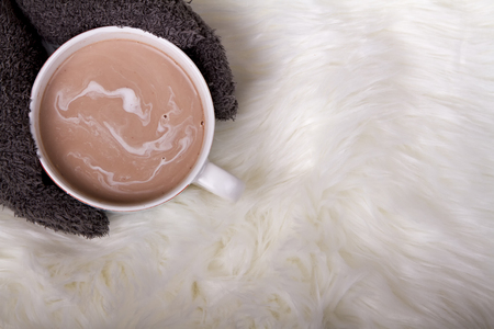 A person holding a mug of hot chocolate or cocoa on a faux fur background  Foto de archivo
