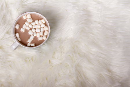 A mug of hot chocolate or cocoa with marshmallows on a faux fur background  Foto de archivo