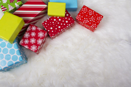 Red, White, Blue and Green Christmas presents on a faux fur background. Foto de archivo