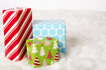 Red, White, Blue and Green Christmas presents on a faux fur background.