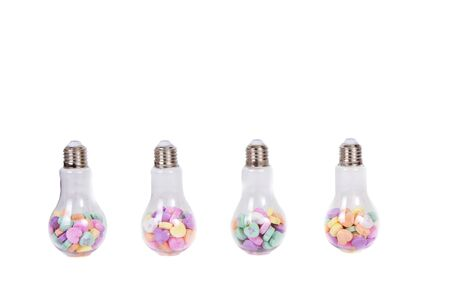 Conversation hearts in a light bulb container isolated on white.