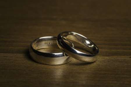 Silver Wedding Rings on a wooden background 免版税图像