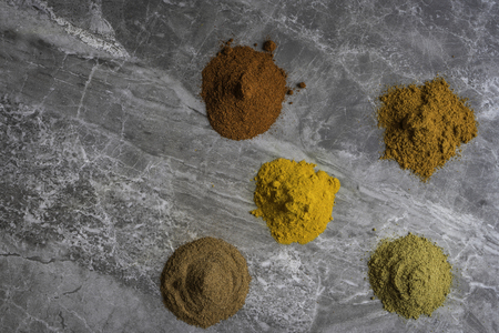 Dried mixed organic spice powders on a marble kitchen worktop background photographed from above Standard-Bild