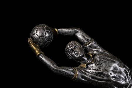 A silver trophy of a football (soccer) goalkeeper with gold accents on a black background for a presentation ceremony