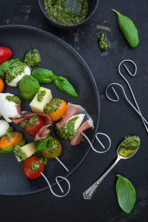 Aperitif skewer with tomatoes, cheese, ham, mozzarella and pesto on a plate on an old dark background