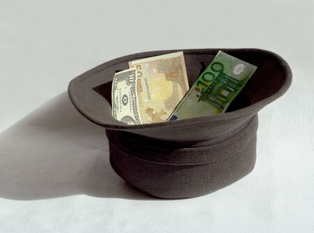 penury: A hat for charity with money Stock Photo