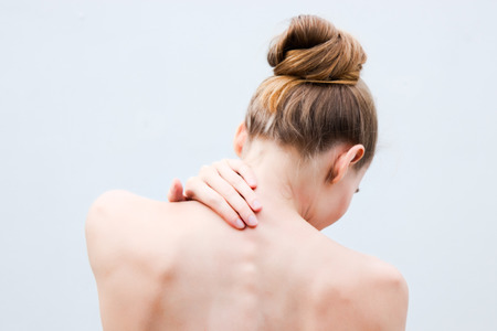 Young woman having pain in the back and neck. Health-care Concept. 스톡 콘텐츠