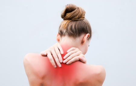 Young woman having pain in the back and neck. Health-care Concept. Stock fotó