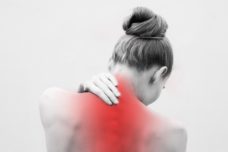 Young woman having pain in the back and neck. Health-care Concept. close up black and white Фото со стока