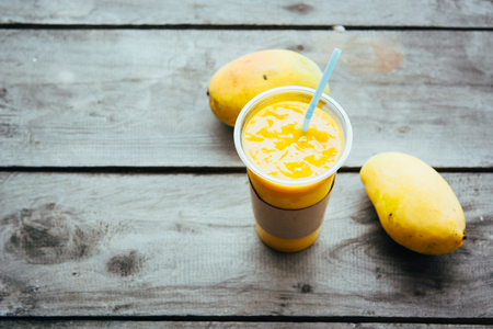 Mango smoothie in glass and mango fruits on wooden table Fruit shake background. Healthy drink recepie.