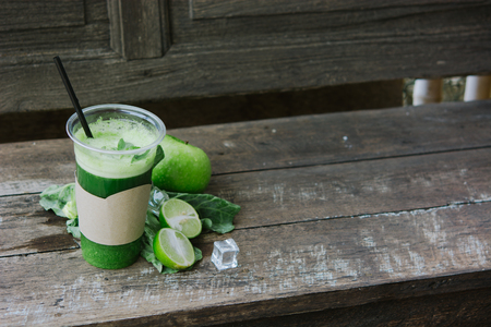 Green apple smoothie in glass and kale leaves on rustic wooden table. Summer Detox shake background with copy space. Healthy drink recepie. 写真素材