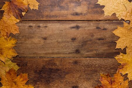 Autumn leaves on rustic wooden background. Top view with copy space. Wallpaper for Halloween party and seasonal rural festival.