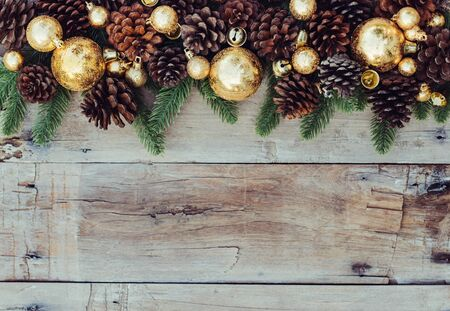Christmas wooden background with pinecone and golden balls. New year concept. Top view with copy space. Foto de archivo
