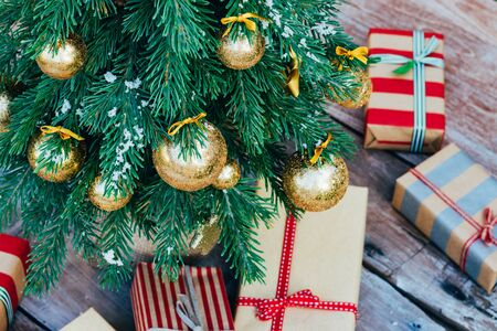 Christmas background. Green fir tree with golden balls and gift boxes. Foto de archivo