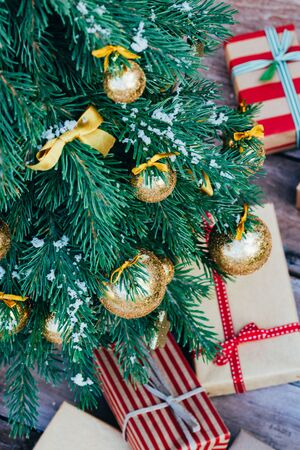 Merry christmas background. Green fir tree with golden balls, gift boxes and ribbon.
