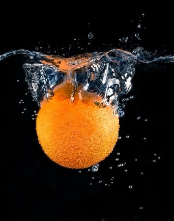 fr�chte in wasser: Orange Spritzen auf schwarzem Hintergrund