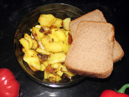fried potatoes: Fried potatoes, marinated mushrooms, tomato and pepper on a black background