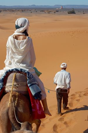 the woman and its guide going across sahara photo