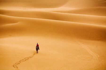 a group of people travelling into desert photo