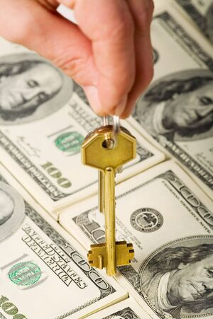 Hand holding a golden key over dollar background  photo