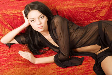A beautiful young woman lying on red bed on the black cloth  photo