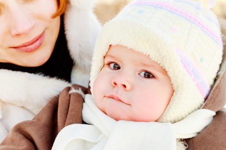 ropa de invierno: La mujer con el beb� en su mano en el invierno