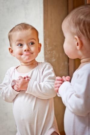 Baby die zich tegen de spiegel