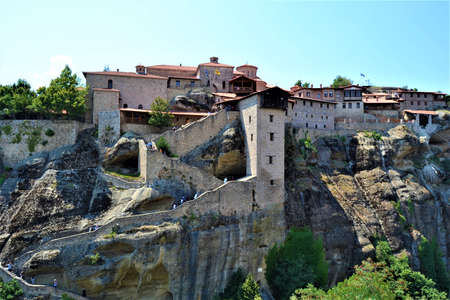 Meteora Land in the Sky: Great ancient city of Meteora in Greece. Trees, vintage houses, blue sky and white clouds.