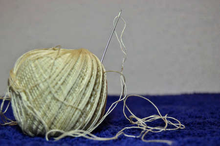Close up Needle and yellow thread. Details of a thread and it can be observed its winding geometry