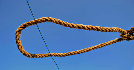 Rope and blue sky background. A rope tied off as sailor's knot.
