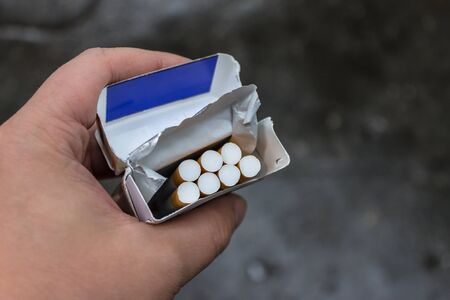 A pack of cigarettes in his hands