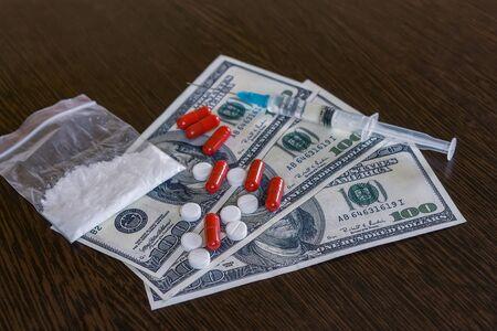 Una bolsa de narcóticos en polvo y pastillas sobre la mesa con billetes Foto de archivo