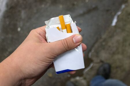 Smoker is holding a pack of cigarettes Stock Photo