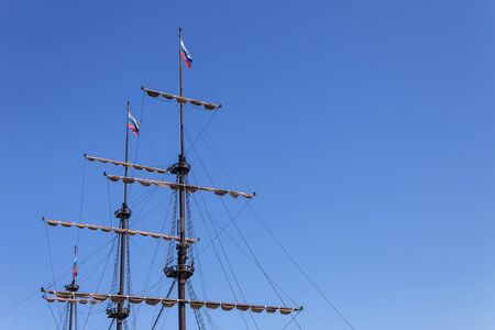 Mast of the ship with raised sails against the blue sky with flags Banco de Imagens