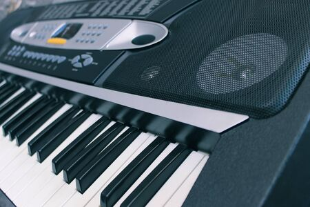 Close-up of a musical electronic synthesizer and its keys with a speaker
