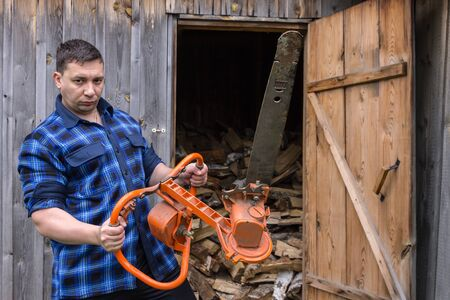 Farmer in a blue shirt with a big chainsaw on a background of a wooden warehouse