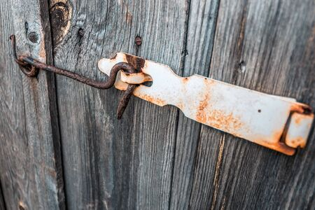 Old and rusty hook locks the old dried up wooden barn door