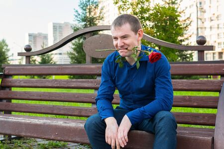 A man with a rose in his teeth sits on a park bench and looks at women Reklamní fotografie