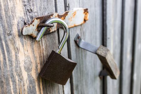 An open padlock hanging from the doors of an old wooden barn