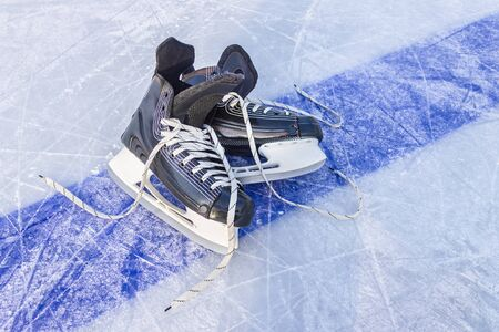 Sports black skates are on the hockey court. Winter sports equipment