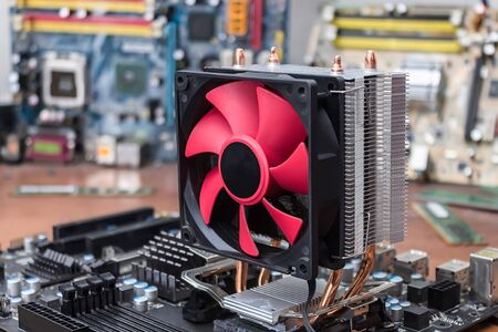 A broken motherboard cooling system due to dust is under repair in a computer workshop