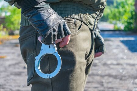 Handcuffs on the belt of a policeman who is preparing to pull them out and apply Banque d'images