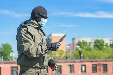 Armed man with a knife in a balaclava, black glasses and a medical mask in profile