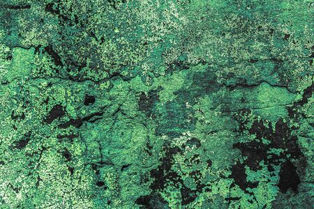 Texture, background of green concrete wall in cracks and damage with cracked old paint