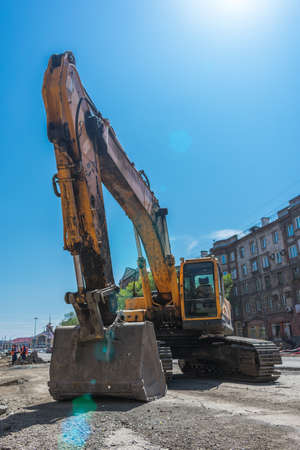 Excavator and his big bucket during the construction of the road against the backdrop of urban buildings
