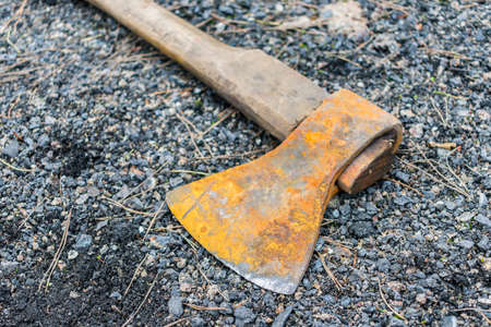 A rusty ax lies on the ground on fine gravel and pebbles