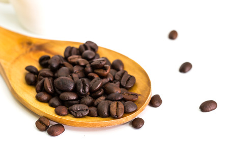 Coffee beans in wooden spoon, close up photo